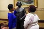 Joyce Amos, left, and Pamela Johnson, who both work in the office of Maryland House Speaker Adrienne Jones, inspect a bronze statue of abolitionist Frederick Douglass during a private viewing ahead of its unveiling at the Maryland State House, Monday, Feb. 10, 2020, in Annapolis, Md. The statue, along with a statue of Harriet Tubman, will be unveiled Monday night in the Old House Chamber, the room where slavery was abolished in Maryland in 1864. (AP Photo/Julio Cortez)