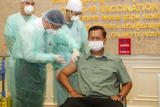 Cambodia's Lt. Gen. Hun Manet, right, a son of Prime Minister Hun Sen, receives a shot of the COVID-19 vaccine at Calmette hospital in Phnom Penh, Cambodia, Wednesday, Feb. 10, 2021. Cambodia began its inoculation campaign against the COVID-19 virus with vaccines donated from China, the country's closest ally. (AP Photo/Heng Sinith)