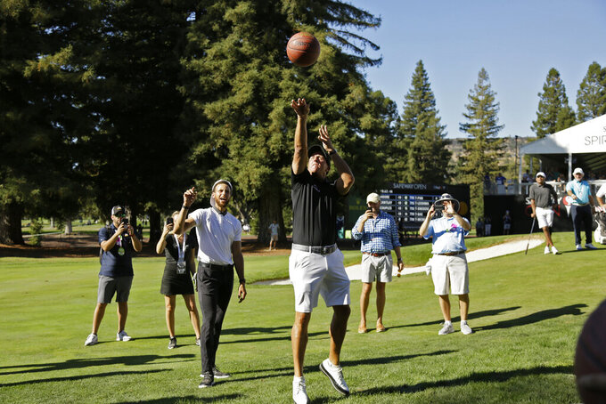 Phil Mickelson shoots a basketball below the 17th green of the Silverado Resort North Course as Stephen Curry looks on during the pro-am at the Safeway Open PGA golf tournament Wednesday, Sept. 25, 2019, in Napa, Calif. (AP Photo/Eric Risberg)