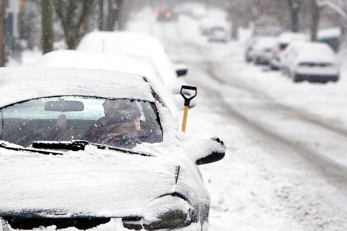 Ron Brooks has a hard time driving his car out of the spot he parked on Maple Street in New Bedford, Tuesday, December 3, 2019 after heavy snow fell across the region. (Peter Pereira/Standard Times via AP)