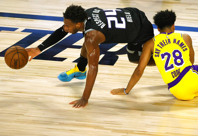 Sacramento Kings' Buddy Hield (24) grabs the ball after colliding with Los Angeles Lakers' Quinn Cook (28) during the second quarter of an NBA basketball game Thursday, Aug. 13, 2020, in Lake Buena Vista, Fla. (Kevin C. Cox/Pool Photo via AP)