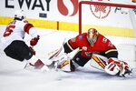 New Jersey Devils' Jack Hughes, left, scores on Calgary Flames goalie David Rittich during the first period of an NHL hockey game Thursday, Nov. 7, 2019, in Calgary, Alberta. (Jeff McIntosh/The Canadian Press via AP)