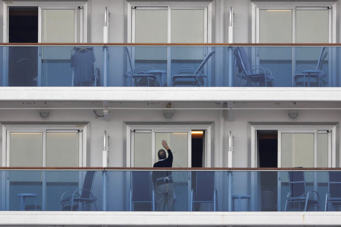 A passenger cleans the window of his cabin on the quarantined Diamond Princess cruise ship Saturday, Feb. 15, 2020, in Yokohama, near Tokyo. A viral outbreak that began in China has infected more than 67,000 people globally. The World Health Organization has named the illness COVID-19, referring to its origin late last year and the coronavirus that causes it. (AP Photo/Jae C. Hong)