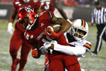 Syracuse defensive back Christopher Fredrick,  right, attempts to bring down Louisville running back Javian Hawkins (10) during the second half of an NCAA college football game in Louisville, Ky., Saturday, Nov. 23, 2019. (AP Photo/Timothy D. Easley)
