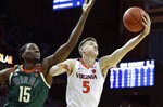 Virginia guard Kyle Guy (5) barbs a rebound next to Miami center Ebuka Izundu (15) during an NCAA college basketball game Saturday, Fe b. 2, 2019, in Charlottesville, Va. (AP Photo/Andrew Shurtleff)