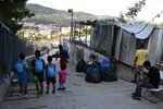 Migrants leave from an overcrowded refugee camp at the port of Vathy on the eastern Aegean island of Samos, Greece, Monday, Sept. 20, 2021. The transfer of all the migrants to the new €43 million ($50 million) closed monitored facility began Monday and be completed by Wednesday. (AP Photo/Michael Svarnias)