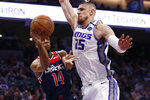 Washington Wizards guard Ish Smith, left, passes as Sacramento Kings center Alex Len defends during the first quarter of an NBA basketball game in Sacramento, Calif., Tuesday, March 3, 2020. (AP Photo/Rich Pedroncelli)