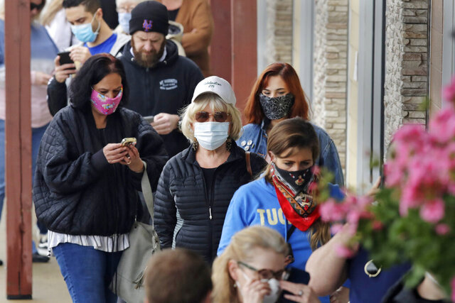 Shoppers, many wearing protective masks due to the COVID-19 virus outbreak, wait in line at a Whole Foods store in Bedford, New Hampshire, Friday, May 1, 2020. (AP Photo/Charles Krupa)