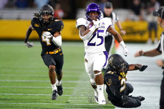 East Carolina running back Kingston McKinstry heads to the end zone for a touchdown, between Appalachian State defensive backs Nick Ross, left, and Ryan Huff during the first half of an NCAA college football game Thursday, Sept. 2, 2021, in Charlotte, N.C. (AP Photo/Chris Carlson)
