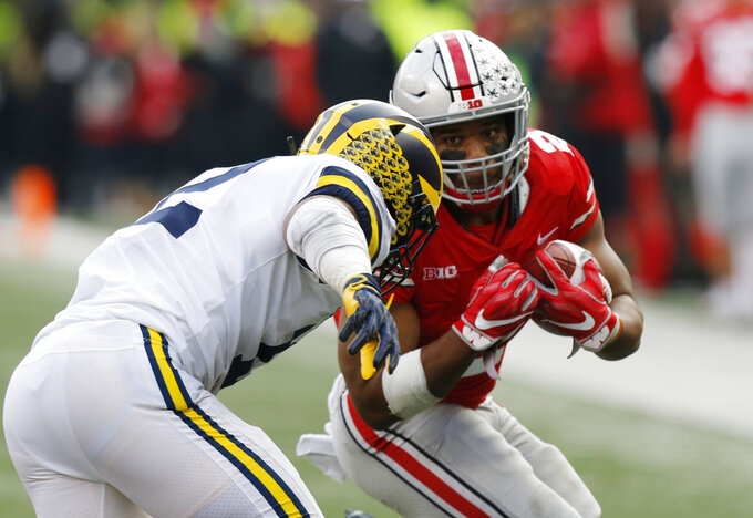 Ohio State running back J.K. Dobbins, right, cuts up field against Michigan linebacker Josh Ross during the second half of an NCAA college football game Saturday, Nov. 24, 2018, in Columbus, Ohio. Ohio State beat Michigan 62-39. (AP Photo/Jay LaPrete)