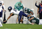 Utah State quarterback Jordan Love, left, is tripped by Michigan State's Matt Morrissey (10) and Josh Butler (19) during the second quarter of an NCAA college football game, Friday, Aug. 31, 2018, in East Lansing, Mich. (AP Photo/Al Goldis)
