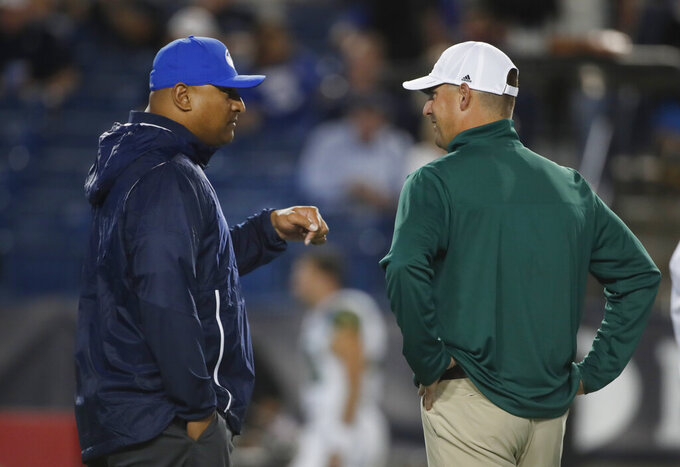 BYU head coach Kalani Sitake, left, and South Florida head coach Jeff Scott, right, talk before playing in an NCAA college football game Saturday, Sept. 25, 2021, in Provo, Utah. (AP Photo/George Frey)