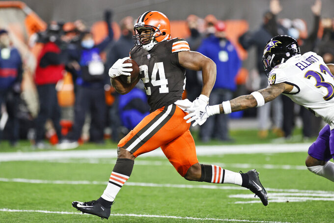 Cleveland Browns running back Nick Chubb (24) rushes for a 14-yard touchdown as Baltimore Ravens free safety DeShon Elliott (32) reaches for him during the first half of an NFL football game, Monday, Dec. 14, 2020, in Cleveland. (AP Photo/Ron Schwane)