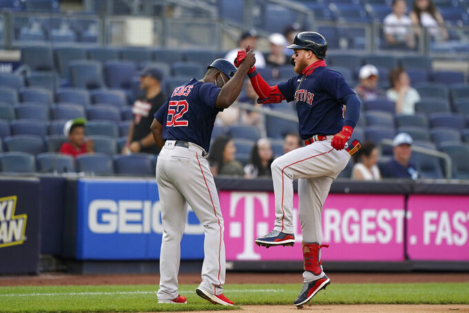 Boston Red Sox Alex Verdugo, right, celebrates with third base coach Carlos Febles, left, after hitting a solo home run during the first inning of a baseball game, Sunday, June 6, 2021, at Yankee Stadium in New York. (AP Photo/Kathy Willens)