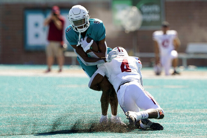 Coastal Carolina wide receiver Tyler Roberts is tackled by Massachusetts defensive back Noah Boykin during the second half of an NCAA college football game on Saturday, Sept. 25, 2021, in Conway, S.C. (AP Photo/Chris Carlson)