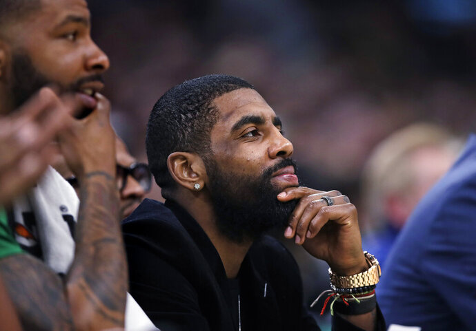 Boston Celtics guard Kyrie Irving, center, who is sidelined with a hip strain, watches play from the bench with forward Marcus Morris, left, during the first quarter of the team's NBA basketball game against the Charlotte Hornets in Boston, Wednesday, Jan. 30, 2019. (AP Photo/Charles Krupa)