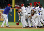 Texas Rangers' Nomar Mazara, left, and teammates mob Nick Solak, second from left dropping his helmet, after Solak reached first on a fielding error by Los Angeles Angels' Albert Pujols that allowed Delino DeShields to score in the 11th inning of a baseball game in Arlington, Texas, Tuesday, Aug. 20, 2019. The Rangers won 3-2. (AP Photo/Tony Gutierrez)