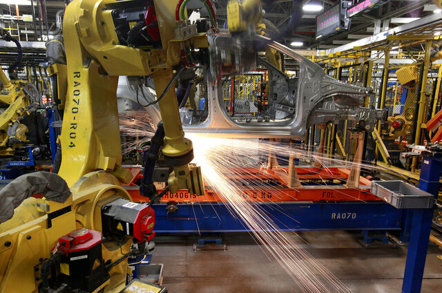 In this May 19, 2011 photo, robots weld a Chevrolet Sonic at the General Motors Orion Assembly plant in Orion Township, Mich. General Motors, Ford, jet engine maker Rolls-Royce and other companies are talking to their governments about repurposing idled factories to produce vital goods to fight the coronavirus such as ventilators and surgical masks. On Friday, March 20, 2020 President Donald Trump invoked the Korean War-era Defense Production Act, allowing the government to marshal the private sector to fight the COVID-19 pandemic. Although it allows the government to steer factories to overcome shortages, makers of heavy goods such as cars and trucks can't just flip a switch and produce something else. (AP Photo/Paul Sancya)