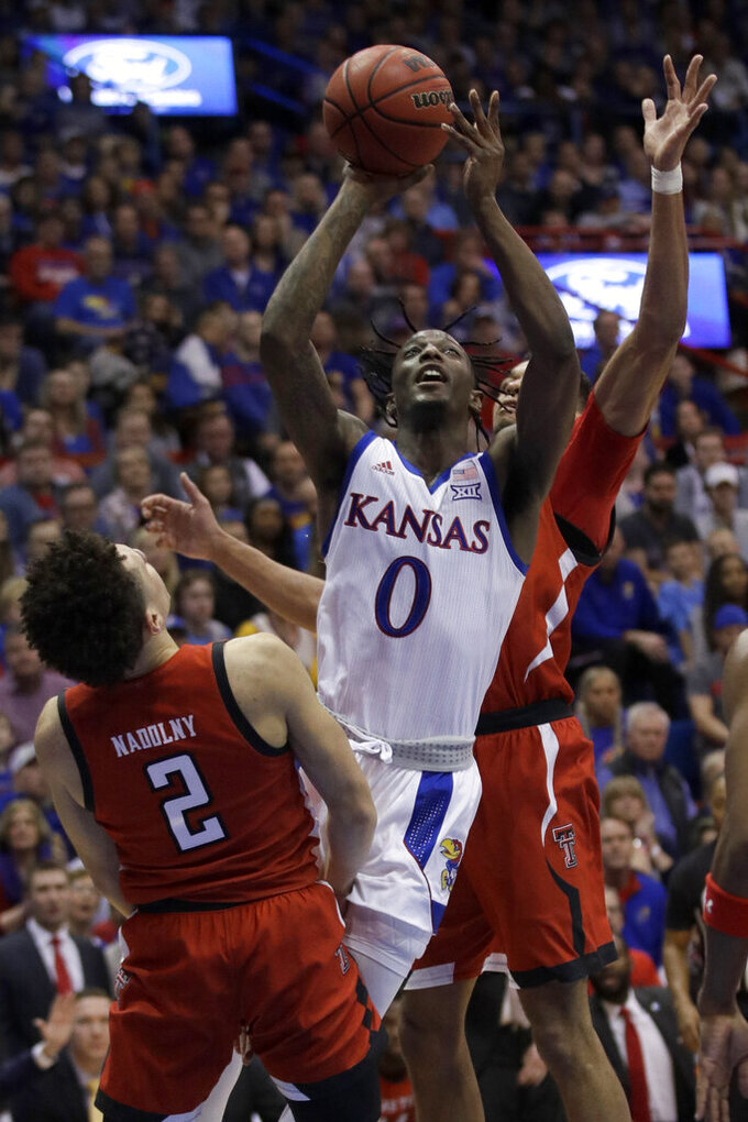 Kansas guard Marcus Garrett (0) shoots over Texas Tech guard Clarence Nadolny (2) while covered by forward TJ Holyfield, back, during the first half of an NCAA college basketball game in Lawrence, Kan., Saturday, Feb. 1, 2020. (AP Photo/Orlin Wagner)