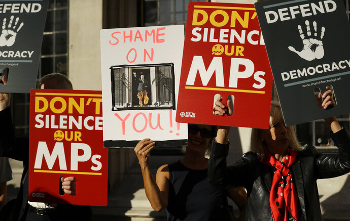 Protesters hold banners outside the Supreme Court in London, Tuesday Sept. 17, 2019. The Supreme Court is set to decide whether Prime Minister Boris Johnson broke the law when he suspended Parliament on Sept. 9, sending lawmakers home until Oct. 14 — just over two weeks before the U.K. is due to leave the European Union. (AP Photo/Matt Dunham)