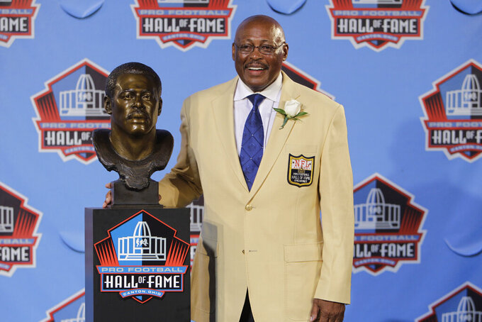 FILE - In this Aug. 7, 2010 file photo, Floyd Little poses with his bust after enshrinement in the Pro Football Hall of Fame in Canton, Ohio.   Little, the Hall of Fame running back who starred at Syracuse and for the Denver Broncos, has died.  The Pro Football Hall of Fame said he died Friday, Jan. 1, 2021.   (AP Photo/Mark Duncan, File)