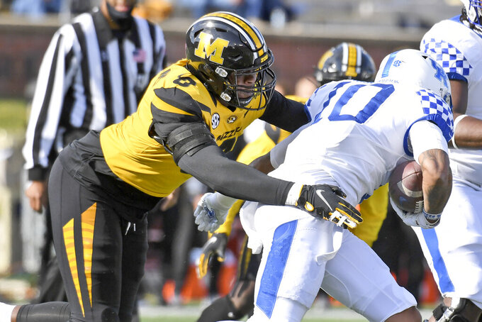 Missouri defensive lineman Tre Williams, left, reaches for Kentucky running back Asim Rose Jr., right, during the first half an NCAA college football game Saturday, Oct. 24, 2020, in Columbia, Mo. (AP Photo/L.G. Patterson)