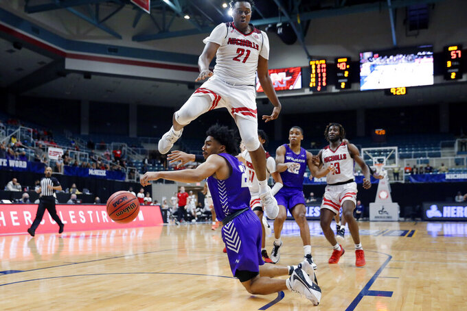 Abilene Christian guard Coryon Mason, below, loses the ball on a drive to the basket under Nicholls State center Ryghe Lyons (21) during the second half of an NCAA college basketball game for the Southland Conference men's tournament championship Saturday, March 13, 2021, in Katy, Texas. (AP Photo/Michael Wyke)