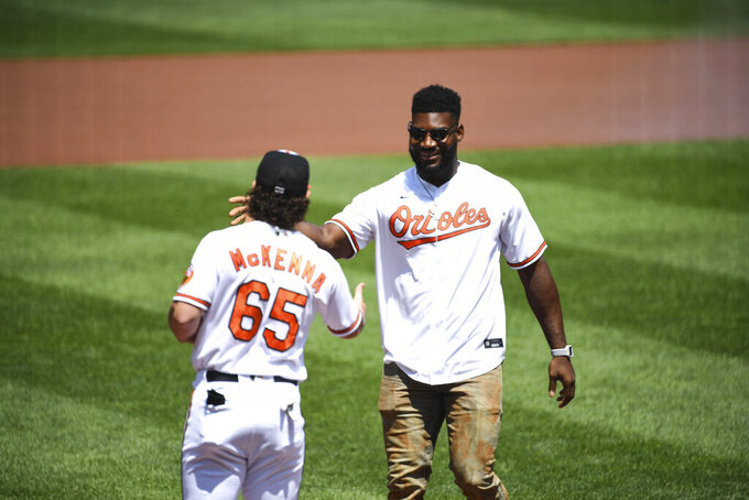 Baltimore Ravens' Tyus Bowser, right, is greeted by Baltimore Orioles' Ryan McKenna (65) after throwing out the ceremonial first pitch before a baseball game between the Orioles and the Tampa Bay Rays, Sunday, Aug. 8, 2021, in Baltimore. (AP Photo/Terrance Williams)