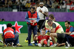 """FILE - In this Oct. 9, 2019, file photo, Wales' Dan Biggar is assisted after he was injured during the Rugby World Cup Pool D game at Oita Stadium between Wales and Fiji in Oita, Japan. A """"shadow trial"""" of advanced eye-tracking technology will be conducted in the Trans-Tasman Super Rugby tournament in Australia and New Zealand as part of World Rugby's bid to tackle head injuries by improving the detection of concussion. (AP Photo/Aaron Favila, File)"""