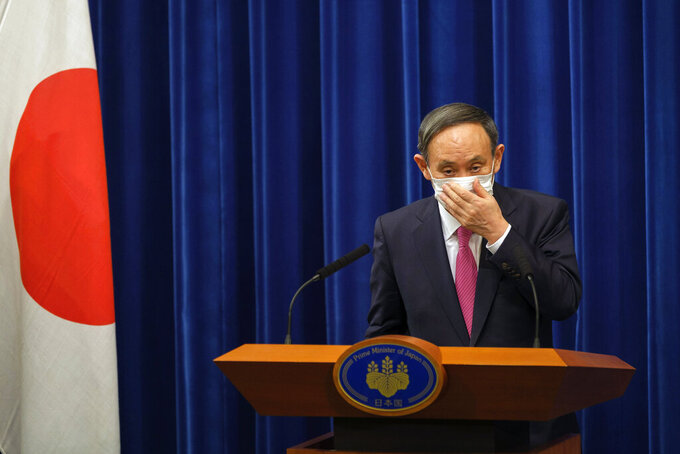 FILE - In this Dec. 25, 2020, file photo, Japan's Prime Minister Yoshihide Suga adjusts a face mask after a press conference on the COVID-19 situation in Japan at the prime minister's office in Tokyo. Prime Minister Suga came to office on a surge of popularity, pledging to combat the coronavirus and fix the languishing economy. Now his support ratings have plunged amid flaring virus outbreaks and scandals within the ruling party, even as the economy appears to be recovering. (Nicolas Datiche/Pool Photo via AP, File)