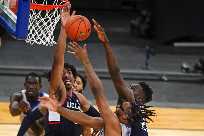 Connecticut's Isaiah Whaley, left, and Adama Sanogo, right, block a shot by Creighton's Denzel Mahoney during the second half of an NCAA college basketball game in the semifinals in the Big East men's tournament Friday, March 12, 2021, in New York. (AP Photo/Frank Franklin II)