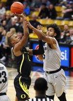 Oregon forward Louis King, left, goes up for a basket as Colorado guard D'Shawn Schwartz defends in the first half of an NCAA college basketball game Saturday, Feb. 2, 2019, in Denver. (AP Photo/David Zalubowski)