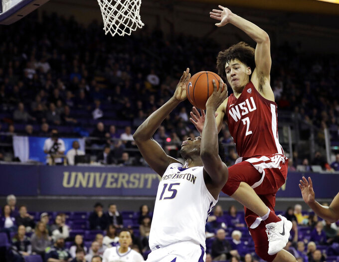 Washington State forward CJ Elleby (2) leaps to block a shot by Washington forward Noah Dickerson (15) during the first half of an NCAA college basketball game, Saturday, Jan. 5, 2019, in Seattle. (AP Photo/Ted S. Warren)