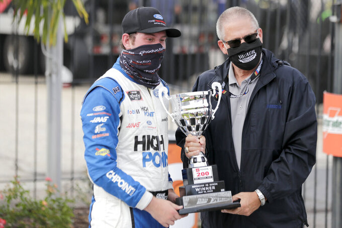 Chase Briscoe is presented with his trophy after winning the NASCAR Xfinity series auto race Thursday, May 21, 2020, in Darlington, S.C. (AP Photo/Brynn Anderson)