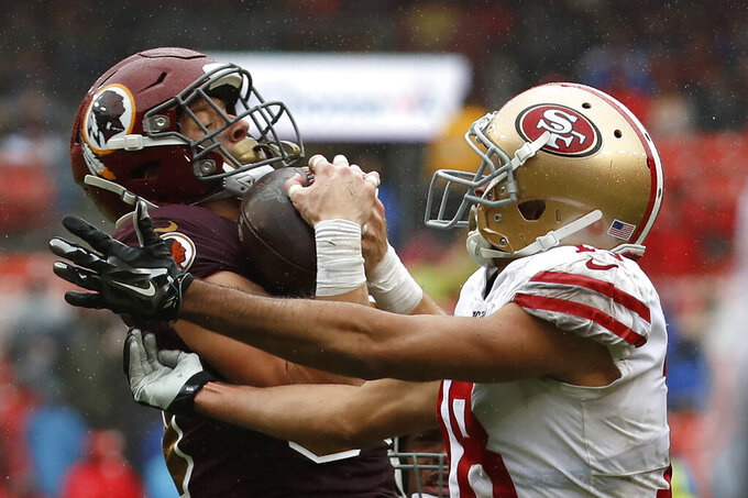 Washington Redskins defensive back Troy Apke, left, intercepts a pass attempt intended for San Francisco 49ers wide receiver Dante Pettis in the second half of an NFL football game, Sunday, Oct. 20, 2019, in Landover, Md. (AP Photo/Alex Brandon)