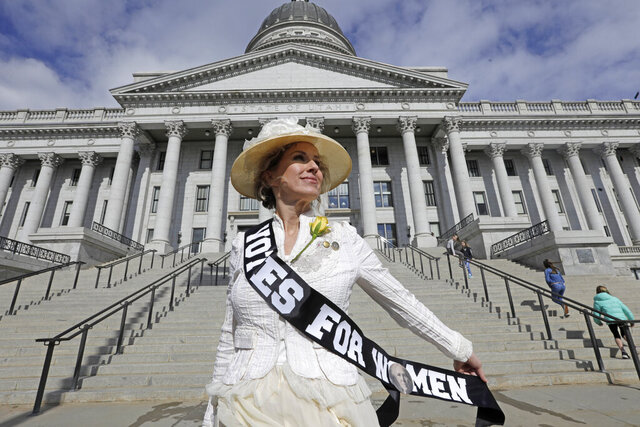 Erin Preston wears period clothing a she stands in front of the rah State Capitol Wednesday, Feb. 12, 2020, in Salt Lake City. Utah lawmakers recognized the 150th anniversary of Utah granting women the right to vote. A Utah woman, Seraph Young, cast the first ballot under a women's suffrage law days after the 1870 law was passed. Utah was also the second state to extend the right to vote to women after Wyoming.(AP Photo/Rick Bowmer)