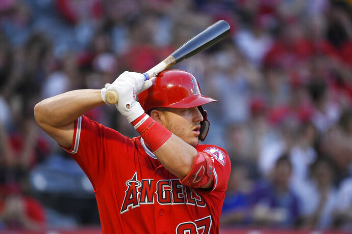 FILE - In this July 25, 2019, file photo, Los Angeles Angels' Mike Trout bats during the first inning of the team's baseball game against the Baltimore Orioles in Anaheim, Calif. Sixty-five players would earn at least $100,000 each time their team wins or loses if the pandemic-delayed major league season get under way, according to an analysis of their contracts by The Associated Press. Trout's salary works out to $222,222 for each game of the 162-game season. (AP Photo/Mark J. Terrill, File)