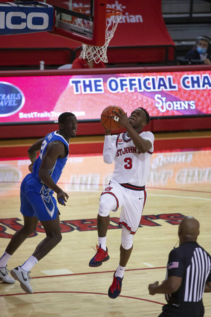 Creighton forward Damien Jefferson, left, watches St. John's guard Rasheem Dunn take a layup during the second half of an NCAA college basketball game Thursday, Dec. 17, 2020, in New York. (AP Photo/Kevin Hagen)