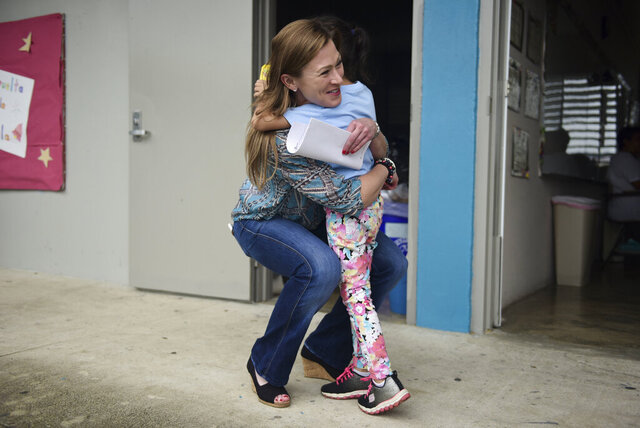 FILE - In this Oct. 13, 2017 file photo, Education Secretary Julia Keleher gets a hug from a student at Ramon Marin Sola Elementary School, in Guaynabo, Puerto Rico. A federal judge on Friday, Feb. 21, 2020, denied a request to move an upcoming corruption trial against Keleher to the U.S. mainland. The former education secretary is in part accused of giving school property to a private company in exchange for living in an upscale apartment complex for six months on a $1 lease even though the agreement stipulated a $1,500 monthly rent. (AP Photo/Carlos Giusti, File)