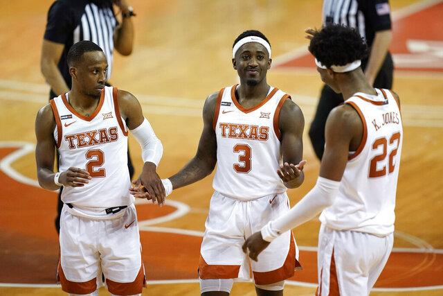 Texas' Courtney Ramey (3) celebrates with teammates Matt Coleman III, left, Kai Jones, right, at the end of an NCAA college basketball game against Iowa State, Tuesday, Jan. 5, 2021, in Austin, Texas. Texas won 78-72. (AP Photo/Eric Gay)