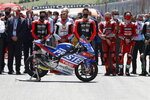 Teammates of 19 years-old Swiss pilot Jason Dupasquier and pilots from other teams stand near his motorbike as they pay a minute of silence in his memory prior to the start of the Motogp Grand Prix of Italy at the Mugello circuit, in Scarperia, Italy, Sunday, May 30, 2021. Dupasquier died Sunday after being hospitalized Saturday, at the Florence hospital following his crash during the qualifying practices of the Moto3. (AP Photo/Antonio Calanni)