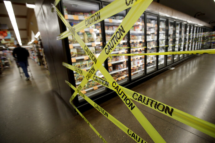 FILE - In this Oct. 31, 2019, file photo, a customer walks past the off-limits frozen foods section of Big John's Market in Healdsburg, Calif., shortly after it reopened and power was restored after being turned off for four days in an attempt to stem fires caused by wind-damaged power lines. Pacific Gas & Electric Corp. CEO Bill Johnson is scheduled to testify during a Legislative oversight hearing on Monday, Nov. 18, at the state Capitol. Lawmakers have repeatedly criticized the bankrupt company for leaving millions of people in the dark for days at a time during dry, windy weather events in October. (AP Photo/Charlie Riedel, File)