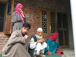 In this Monday, Aug. 26, photo, A Kashmiri man Mohammed Abdullah, center, sits with family members at their home and talks to reporters about his grandson who was picked up in a nocturnal raid recently and shifted to a jail in India's northern city of Agra, in southern Karimabad village, Indian controlled Kashmir. The main city of Indian-controlled Kashmir presents a mostly deserted and subdued look, woven in a maze of razor wire. But drive out into the rural hinterland and residents in village after village narrate horrors of regular nightly raids by Indian army soldiers. The abuses in the nighttime raids by troops began in early August as New Delhi took its action on Kashmir, according to interviews with at least 200 people. The change in status nullified decades-old constitutional provisions that gave Jammu and Kashmir some political autonomy and land inheritance rights. (AP Photo/Aijaz Hussain)