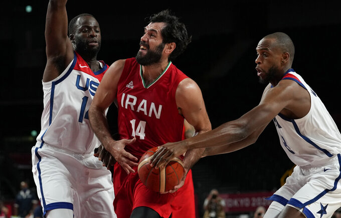 Iran's Mohammadsamad Nik Khahbahrami (14), center, drives between United States' Draymond Green (14), left, and Khris Middleton (8) during men's basketball preliminary round game at the 2020 Summer Olympics, Wednesday, July 28, 2021, in Saitama, Japan. (AP Photo/Eric Gay)