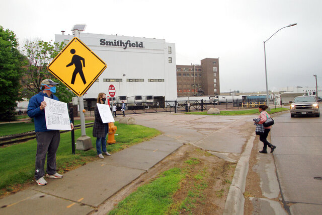 FILE - In this May 20, 2020, file photo, residents cheer and hold thank you signs to greet employees of a Smithfield pork processing plant as they begin their shift in Sioux Falls, S.D. Federal regulators said Thursday, Sept. 10, 2020, they have cited Smithfield Foods for failing to protect employees from exposure to the coronavirus at the company's Sioux Falls plant, an early hot spot for virus infections that hobbled American meatpacking plants. (AP Photo/Stephen Groves, File)