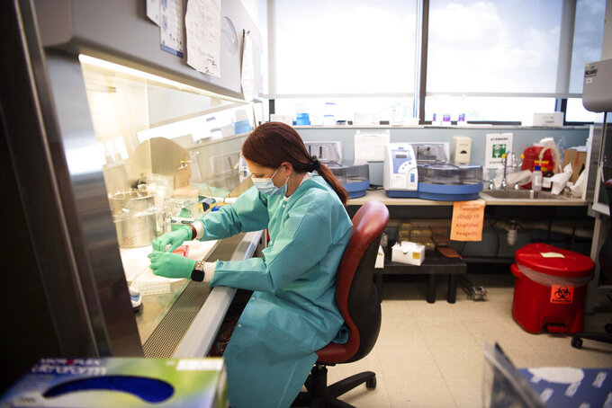 Karen Maynard, a laboratory scientist at the Tennessee public health lab, prepares COVID-19 samples for the extraction of their genetic code as part of the genome sequencing process in Nashville, Tenn., Tuesday, Sept. 14, 2021. (Stephanie Amador/The Tennessean via AP)