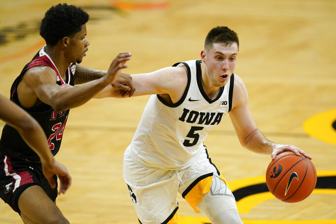 Iowa guard CJ Fredrick drives past Northern Illinois guard Darius Beane, left, during the second half of an NCAA college basketball game, Sunday, Dec. 13, 2020, in Iowa City, Iowa. Iowa won 106-54. (AP Photo/Charlie Neibergall)