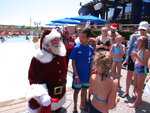 In this July 25, 2019 photo, casino  posing for photos with Santa at the outdoor pool at the Ocean Casino Resort in Atlantic City, N.J. Figures released Aug. 14, 2019 by the New Jersey Division of Gaming Enforcement show the casinos took in $323 million, an increase of 7.8% from July 2018. (AP Photo/Wayne Parry)
