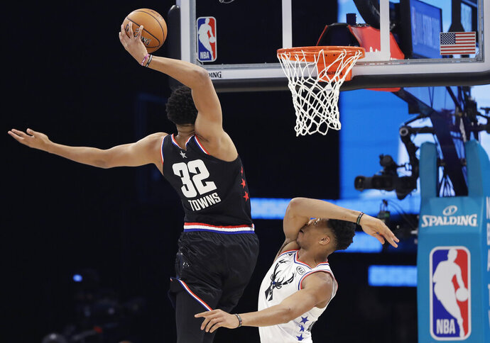 Team LeBron's Karl-Anthony Towns, of the Minnesota Timberwolves, heads to the hoop against Team Giannis' Giannis Antetokounmpo, of the Milwaukee Bucks, during the first half of an NBA All-Star basketball game, Sunday, Feb. 17, 2019, in Charlotte, N.C. (AP Photo/Chuck Burton)