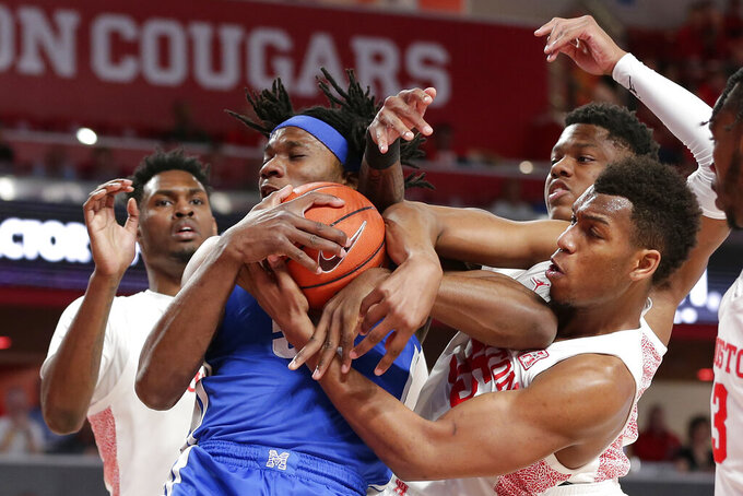 Memphis forward Precious Achiuwa, left middle, wrestles for a rebound with Houston forward Fabian White Jr., right middle, in front of center Chris Harris Jr., left, and guard Marcus Sasser right, during the first half of an NCAA college basketball game Sunday, March 8, 2020, in Houston. (AP Photo/Michael Wyke)